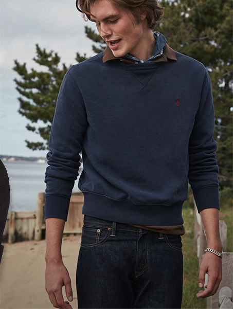 Man wears navy crewneck sweatshirt and dark-wash jeans