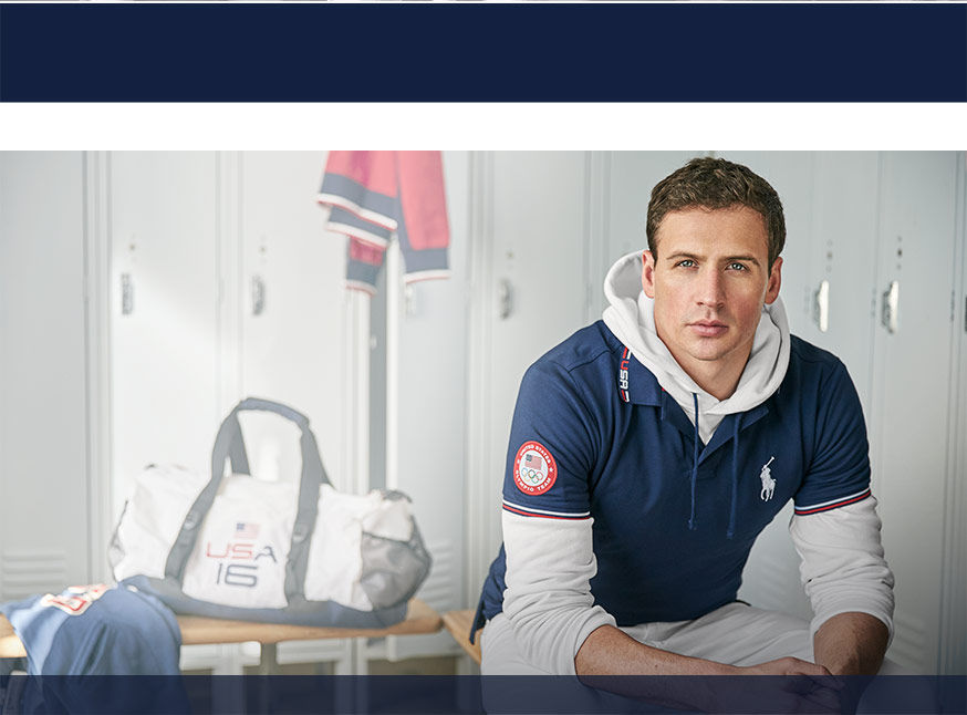 Ryan Lochte, wearing navy polo shirt over white hoodie, sits on bench in locker room; white Team USA duffel in background