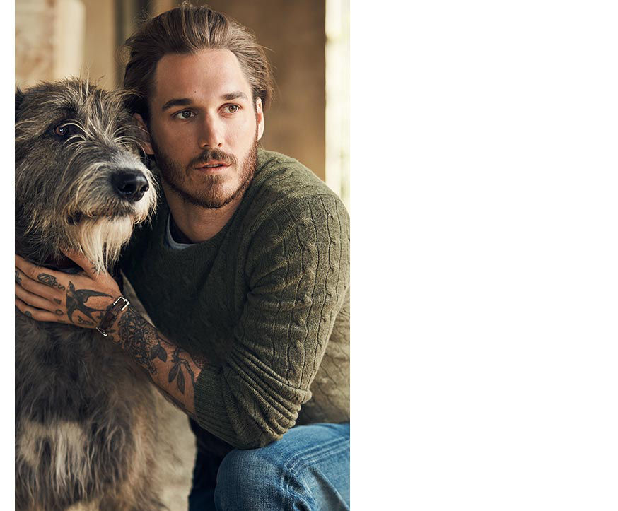 Man wearing sage cable-knit sweater kneels with arms around shaggy grey dog