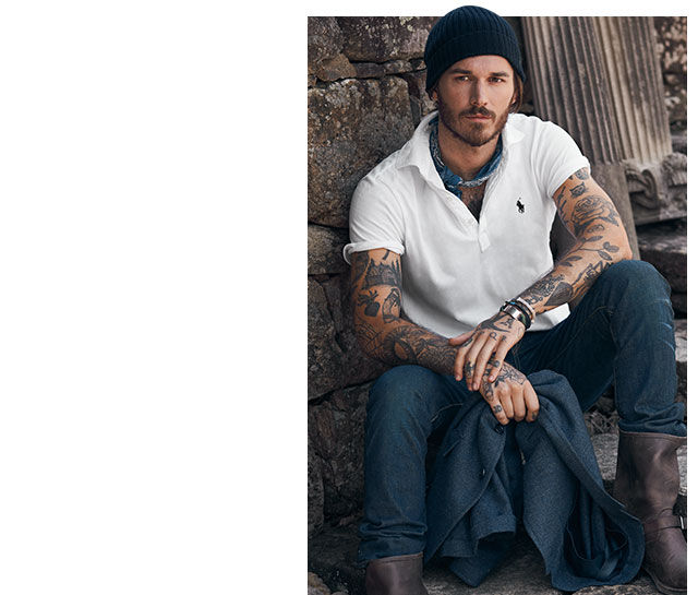 Man with tattoos sits on stone steps while wearing knit hat, a white polo shirt, jeans & moto boots