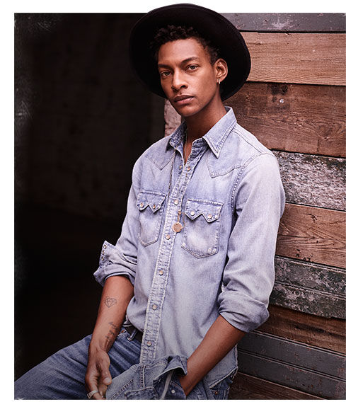 Man wears brimmed hat & denim shirt