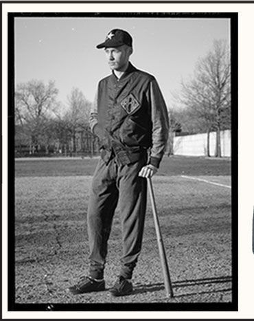 Man in jacket stands on baseball field with bat