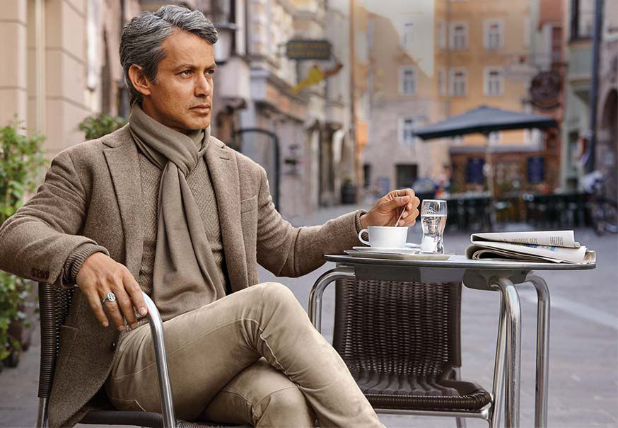 Andrew Lauren wears taupe scarf, blazer, sweater & pant