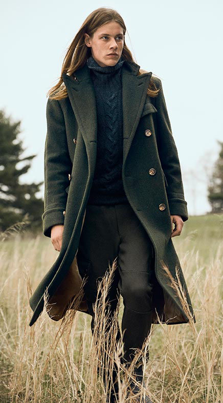 Man layers long green overcoat over blue Aran-knit turtleneck
