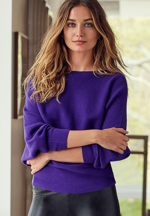 Woman models bright purple dolman-sleeved sweater
