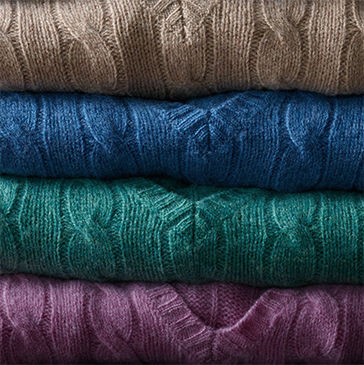 Stack of cable-knit V-neck sweaters in taupe, blue, green & pink