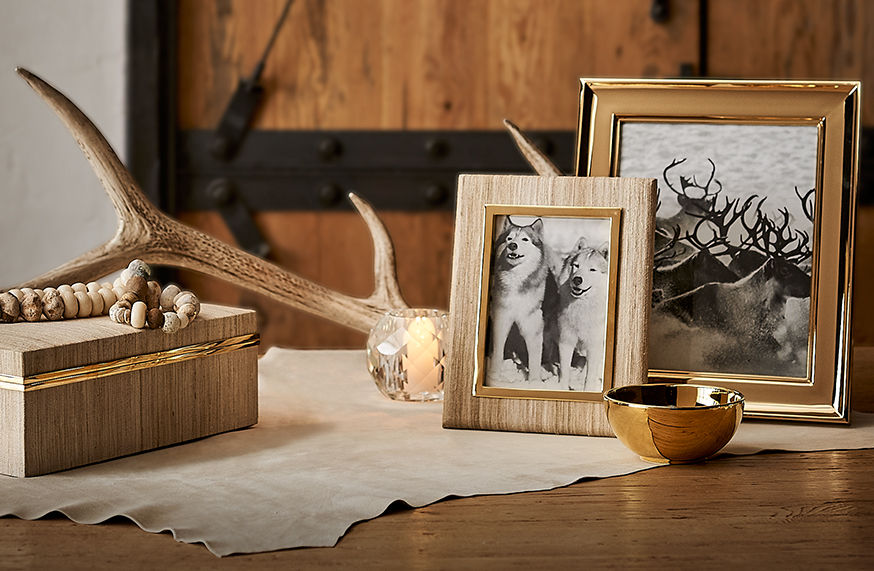 Brass-trimmed picture frames, crystal votive & silk-covered box on tabletop