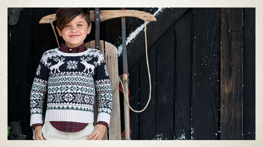 Boy layers Fair Isle sweater over red plaid button-down