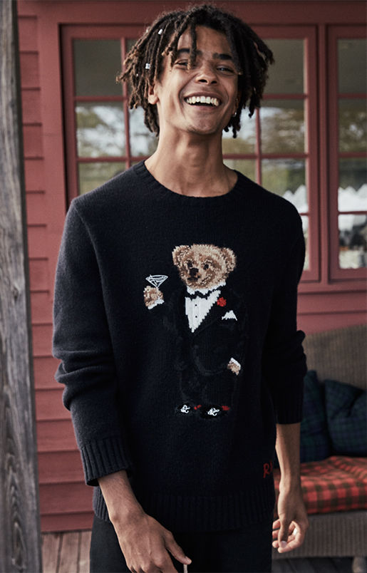 Man wears black sweater knit with Polo bear in tuxedo & holding martini