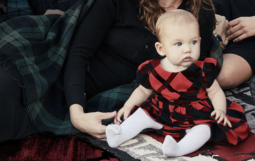 Baby in red puff-sleeve plaid dress & white tights sits with woman