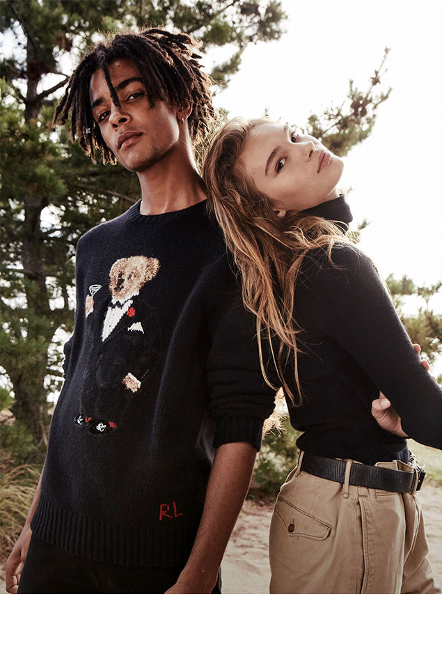 Man wears black Polo Bear sweater & woman wears black turtleneck with oversize chinos