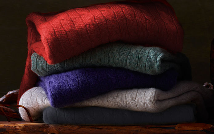 Haphazard stack of cable-knit sweaters in red, light green, purple, white & black