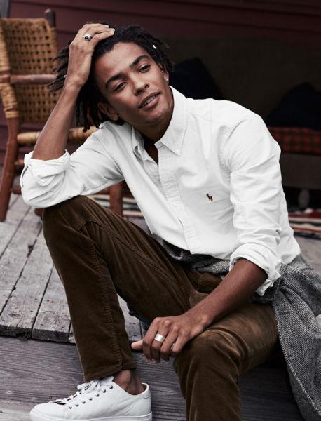 Man sits outside wearing white oxford shirt, brown pants \u0026amp; white sneakers